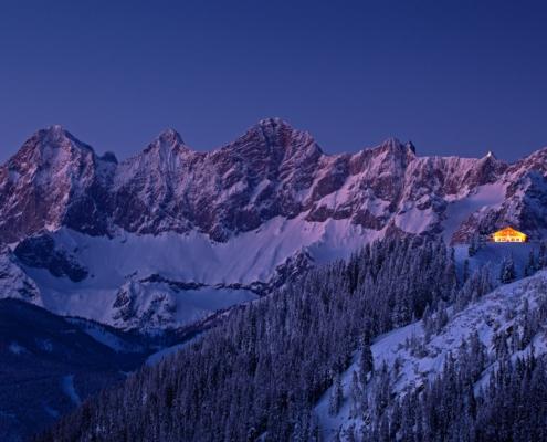 Das verschneite Dachsteinmassiv mit hell erleuchteter Hütte bei Nacht