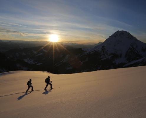 Zwei Skitourengeher überqueren ein Schneefeld bei Sonnenuntergang