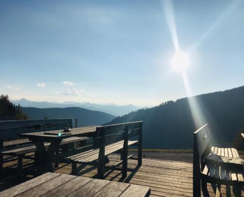 Die Sonne scheint auf die menschenleere Terrasse der Brandalm.
